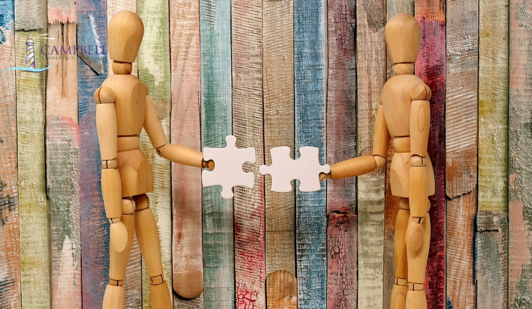 Wooden mannequins holding connecting jigsaw pieces